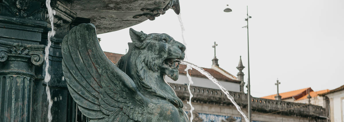 Ancient Winged Lion Fountain in the town square in Porto, Portugal.