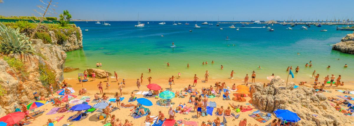 Cascais, Portugal - August 6, 2017: People Sunbathing On Praia D